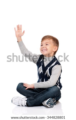 Smiling boy sitting on floor and looks into the distance isolated on white background - stock photo