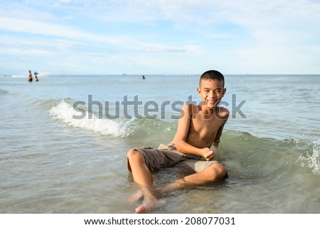 smiling boy sitting on the beach