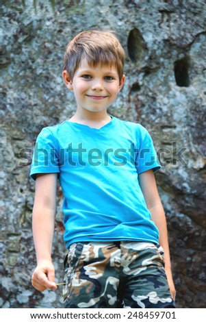 Smiling boy standing near the steep rock - stock photo