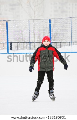 Smiling boy standing on the ice rink outdoors - stock photo