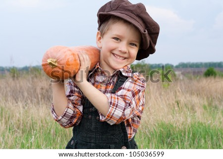 Smiling boy standing with pumpkin on his shoulder in the field - stock photo