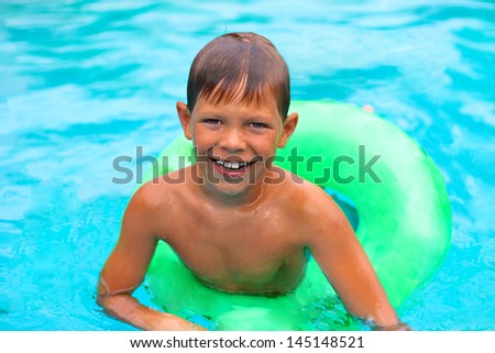 Smiling boy swims in pool on summer vacations - stock photo