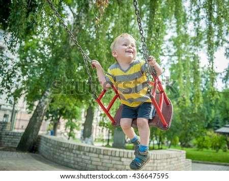 Smiling boy swinging at a playground. Happy boy kid on swing enjoy summer. Childhood, Freedom, Summer Outdoor. Child, Playing, Playground, summer, childhood, leisure and people concept - stock photo