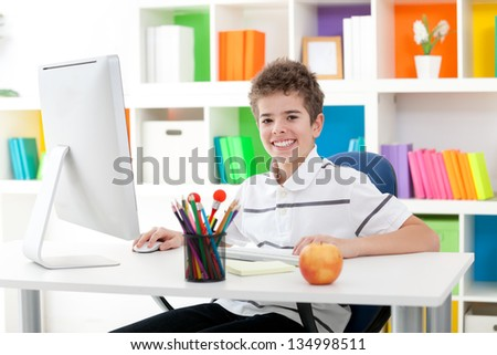 smiling boy using a computer at home - stock photo