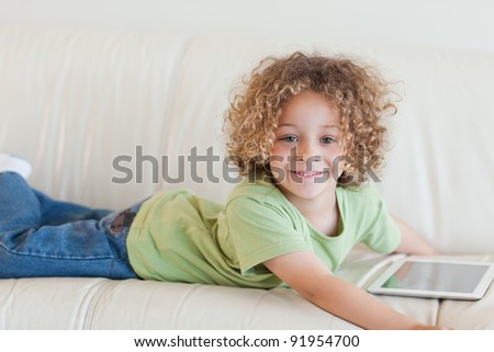 Smiling boy using a tablet computer while lying on a sofa - stock photo