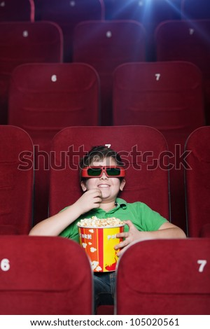 Smiling boy watching 3D movie at the cinema - stock photo