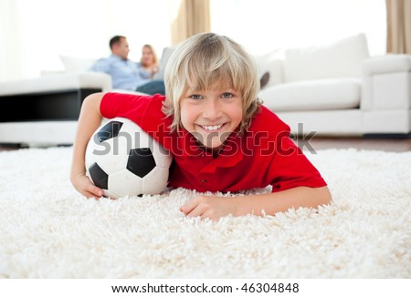 Smiling boy watching football match lying on the floor in the living-room - stock photo