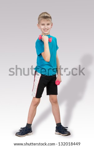 Smiling boy with children's dumbbells on gray background - stock photo