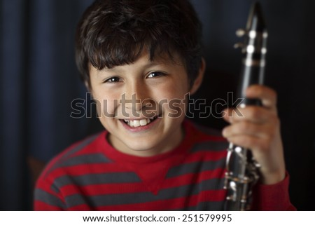 Smiling boy with clarinet - with very shallow depth of field - stock photo