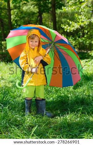 smiling boy with colorful umbrella stands on lawn in  summer park - stock photo