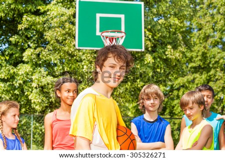 Smiling boy with friends behind during basketball - stock photo