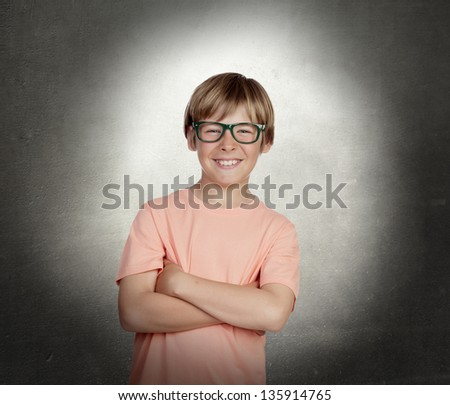 Smiling boy with glasses over a gray background - stock photo