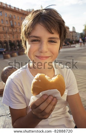 smiling boy with hamburger on city street - stock photo