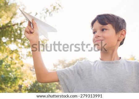 Smiling boy with paper plane in the park on a sunny day