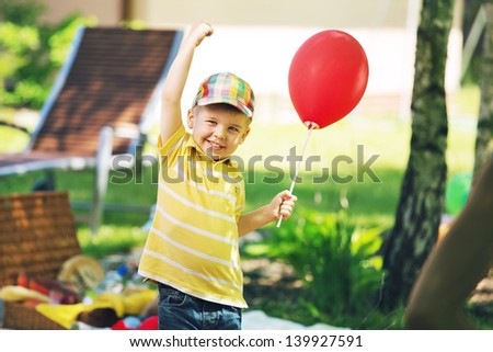Smiling boy with red baloon - stock photo