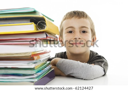 Smiling boy with school books on the table - stock photo