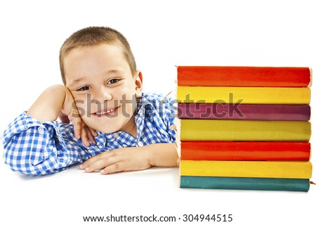 Smiling boy with school books on the table.  Isolated on a white background  - stock photo