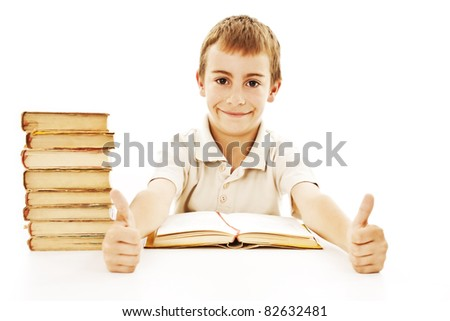 Smiling boy with school books on the table showing thumbs up - stock photo