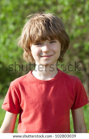 Smiling boy with tousled hair, a sunny day - stock photo
