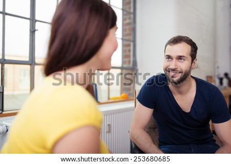 Smiling Boyfriend Listening to Girlfriend While Having a Talk at the Living Room. - stock photo