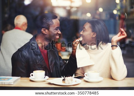 Smiling boyfriend wiping mouth with a napkin his girlfriend during breakfast in modern coffee shop interior, happy young romantic couple having fun together while sitting in cafe bar during free time  - stock photo