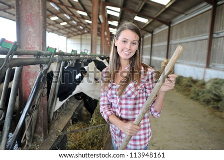 Smiling breeder woman giving food to cows - stock photo