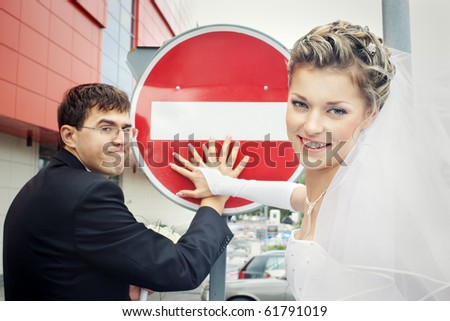 Smiling bride and funny groom with hands on stop sign