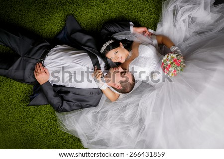 Smiling bride and groom lying on the grass-like carpet. - stock photo