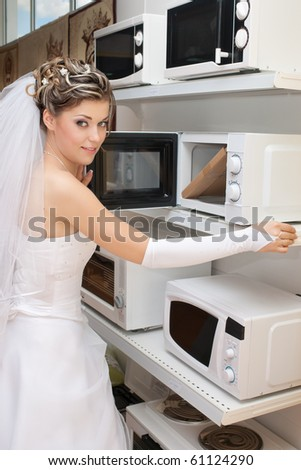 Smiling bride choosing microwave in household appliances store