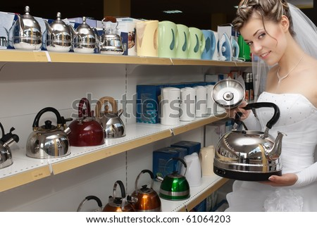 Smiling bride choosing tea pot in household appliances store