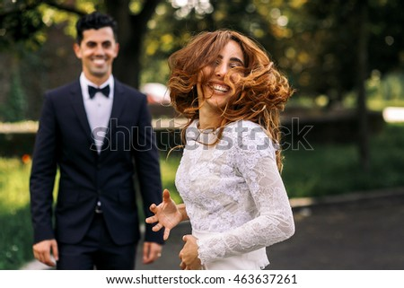 Smiling bride dances before a groom mixing her hair actively