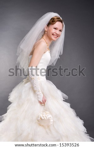 Smiling bride in the studio. In white dress. Isolated over black background - stock photo