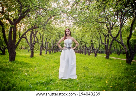 Smiling bride standing in a summer park - stock photo