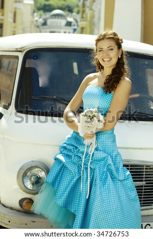 Smiling bride standing near car.