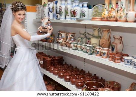 Smiling bride taking a flower vase from ceramics shelf in a store
