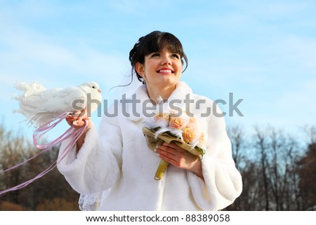 smiling bride with bouquet holds white dove and looks into distance at winter outdoors