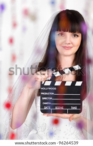 Smiling bride with clapper board stands behind transparent curtain of beads; focus on woman - stock photo