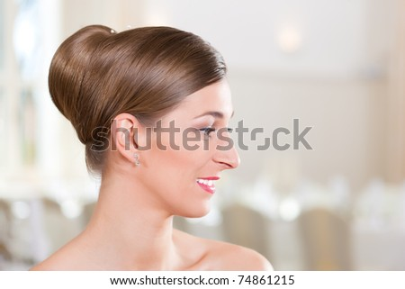 Smiling bride with swept-back hair before the wedding