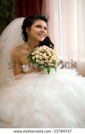 Smiling bride with the bouquet. Focus point on the face & bouquet.