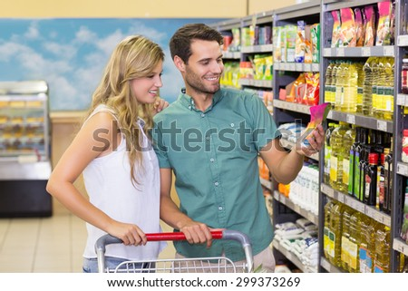 Smiling bright couple buying food products at supermarket - stock photo
