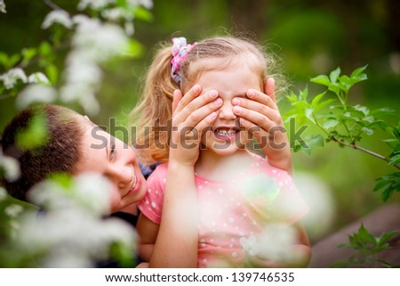 Smiling brother and sister playing in the garden - stock photo