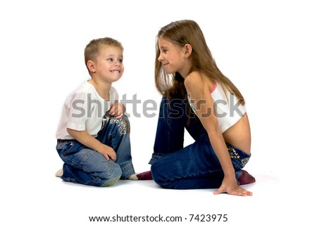 Smiling brother and sister sitting together and talking isolated on white - stock photo