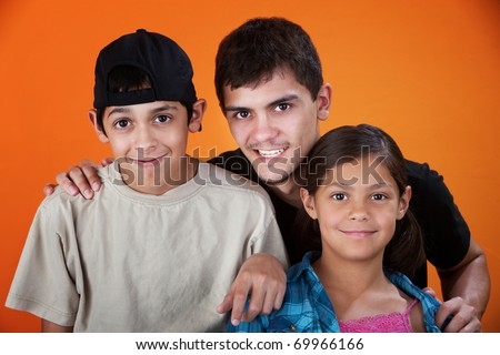 Smiling brothers and sister on an orange background - stock photo