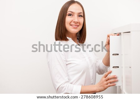 Smiling brunette businesswoman is taking the folder from the cupboard in the office - stock photo
