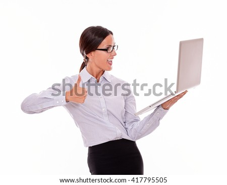 Smiling brunette businesswoman looking at laptop very happy while making a thumb up gesture with one hand and wearing her straight hair back in a button down shirt from waist up on a white background