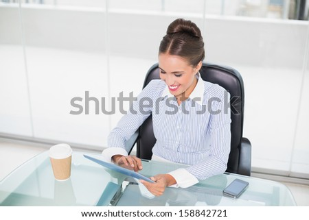 Smiling brunette businesswoman touching tablet in bright office