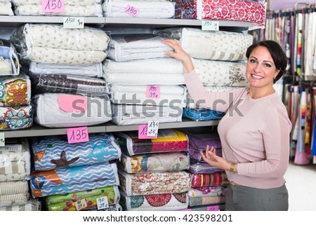 Smiling brunette choosing blanket in textile shop insite - stock photo