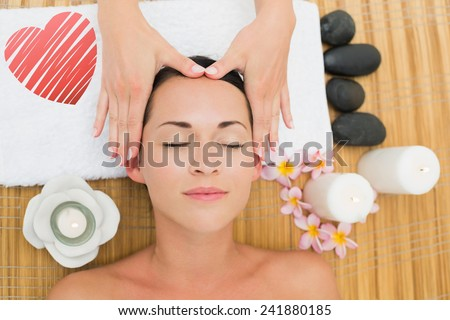 Smiling brunette enjoying a head massage against red heart - stock photo