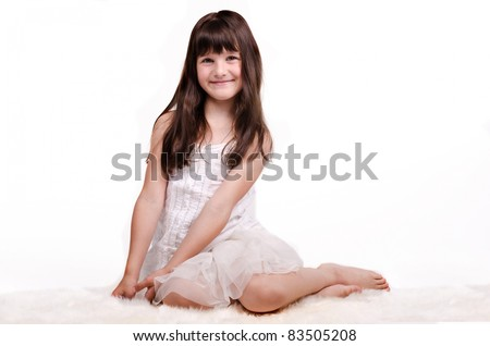 Smiling brunette girl in white dress sitting on white carpet isolated on white background - stock photo