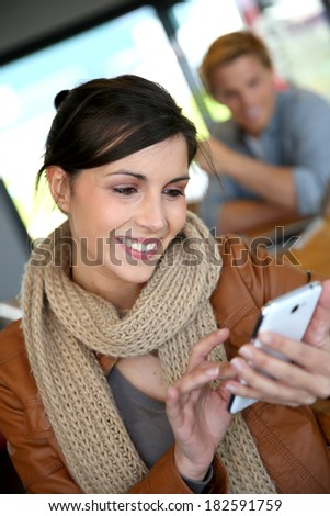 Smiling brunette girl using smartphone in coffee shop - stock photo